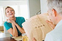 Mature couple at breakfast man reading financial newspaper