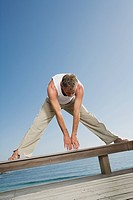 Mature man doing fitness exercises on wooden bench with ocean in background