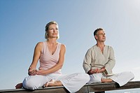 Mature couple sitting cross_legged on wooden bench outdoors doing yoga