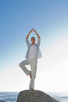 Man standing on one leg, doing yoga on top of rock with ocean in background