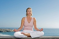 Mature woman sitting cross_legged on wooden bench outdoors doing yoga