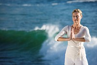 Mature woman standing in prayer position, with waves breaking in background