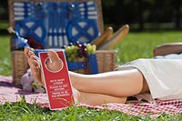 Woman lying on picnic blanket with Do Not Disturb sign hanging from her toe