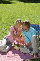 Young couple sitting on Picnic blanket woman feeding man with Radish