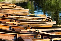 Row of wooden rowing boats moored at side of Kleinhesseloher lake Munich