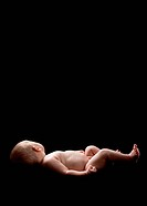 Newborn baby lying on a black background with her face turned away from the camera
