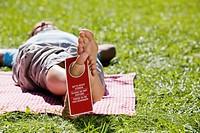 Man lying on picnic blanket, sleeping with Do Not Disturb sign on his foot