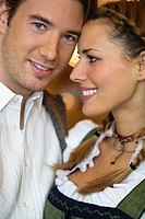 Close_up of young couple in Bavarian costume at Oktoberfest, Munich, Germany