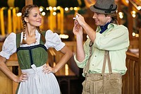 Young man taking photograph of girlfriend at Oktoberfest, Munich, Germany