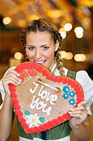 Young woman eating Gingerbread heart at Oktoberfest, Munich, Germany