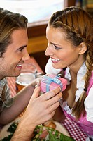 Young man giving present to girl at Oktoberfest beer festival, Munich, Germany