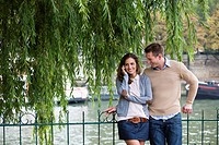 Young couple by river Seine, woman using mobile phone, Paris, France