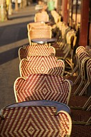 Row of wicker chairs and tables outside cafe, Paris, France
