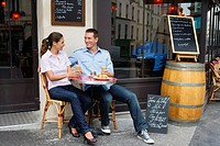 Young couple sitting outside street side cafe, drinking coffee, Paris, France (thumbnail)
