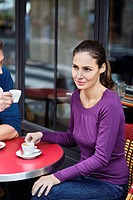 Young couple sitting at cafe table, outdoors, Paris, France