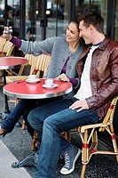Young couple sitting at table outside cafe, woman taking photo, Paris France