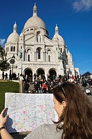 Young woman looking at map in front of Sacre Coeur basilica , Paris, France