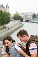 Young couple sitting on bridge, man leaning on woman's back writing postcard