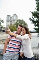 Young couple in front of Notre Dame Cathedral, woman taking photo