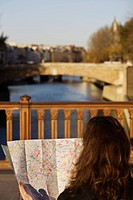 Woman on bridge by river Seine looking at map, Paris, France