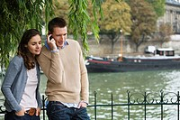 Young couple by river Seine, man using mobile phone, Paris, France