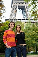 Young smiling couple standing in front of Eiffel tower, Paris, France