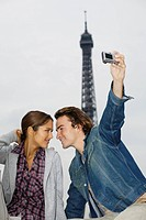 Young couple, man taking photo with digital camera, Eiffel tower in background