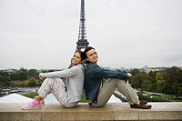Young couple sitting back to back on wall, Eiffel tower in background