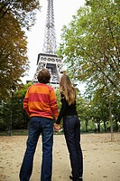 Rear view of young couple standing under Eiffel tower, Paris, France (thumbnail)