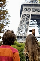 Rear view of young couple taking picture of Eiffel tower, Paris, France