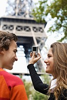 Young couple taking picture of Eiffel tower, Paris, France