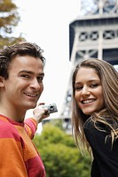 Young couple taking self portrait with Eiffel tower in background, Paris, France (thumbnail)
