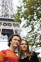 Young couple standing under Eiffel tower, Paris, France