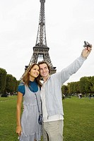 Young couple in front of Eiffel tower, man taking photo, Paris, France (thumbnail)
