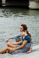 Young couple sitting on steps by river Seine, Paris, France