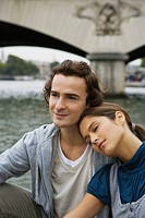 Young couple sitting by river Seine, woman resting head on mans shoulder, Paris