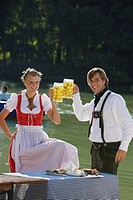 Young couple in traditional Bavarian outfit, toasting with beer glasses, Munich