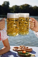 Close_up of young couple drinking beer in Seehaus, beer garden, Munich, Germany