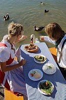 Young couple in traditional Bavarian outfit, feeding swan in beer garden, Munich