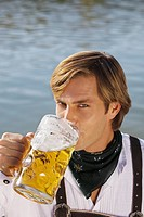 Young man in traditional Bavarian outfit, drinking litre glass of beer, Munich