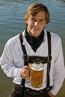 Young man in traditional Bavarian outfit, holding litre glass of beer, Munich