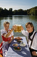 Young couple in traditional Bavarian outfit, having meal in beer garden, Munich