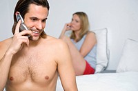 Couple in bedroom ignoring each other