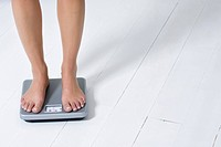Young woman weighing herself (thumbnail)