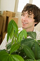 Man carrying house plant (thumbnail)