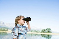 Boy 4_7 standing outdoors using binoculars, lake in background