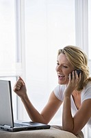 Mature woman smiling and working with Laptop computer using Cell phone