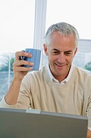 Mature man at computer, holding cup of coffee