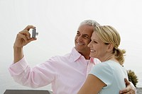 Mature couple smiling while taking self portrait with digital camera