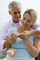 Mature couple, man putting diamond ring on woman's finger